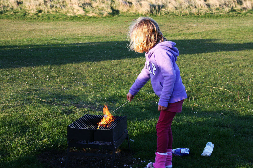 Young girl in a purple fleece is coking marshmallows in a fire made with sticks and branches